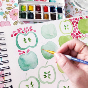 Watercolour painting of green apples, with paintbox and hand holding a paintbrush.